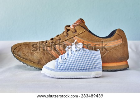 Sneakers of father and son. - stock photo