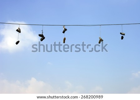 Sneakers on a electric wire - stock photo
