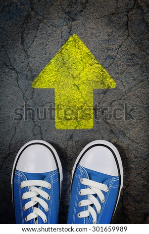 sneakers on cracked concrete surface with painted arrow - stock photo
