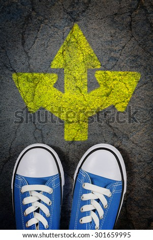 sneakers on cracked concrete surface with painted arrow pointing in three different directions - stock photo