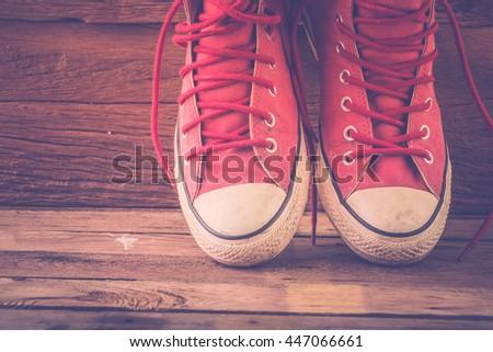 Sneakers on wooden floor, vintage style. - stock photo