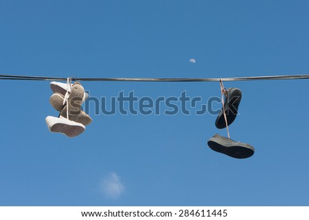 Sneakers tangled in power lines - stock photo