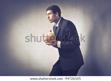 Sneaky businessman holding a money box