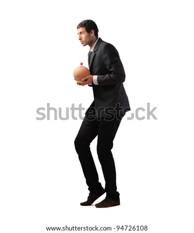 Sneaky businessman holding a money box - stock photo