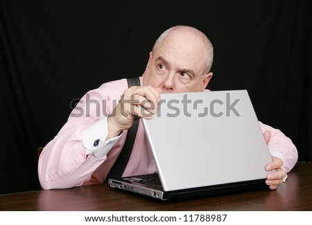 sneaky businessman peeking over a laptop computer good for corporate theft or protection concepts - stock photo