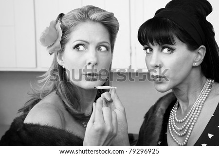Sneaky rich housewives share a marijuana joint in kitchen - stock photo
