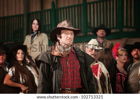 Sneering cowboy in trenchcoat with group of people