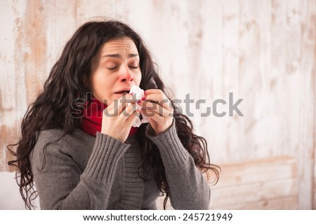 Sneezing beauty. Young sick woman with scarf on her neck sitting in bed and sneezing with her country house on the background - stock photo