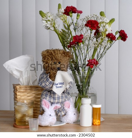 """Sneezing """"Get Well"""" bear in slippers and robe, surrounded by home sick-room necessities. - stock photo"""