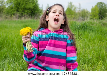 Sneezing girl sitting on green meadow and holding bouquet of dandelions - stock photo