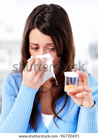 Sneezing girl with pills. On grey background.