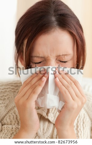 Sneezing young woman in a living room - stock photo