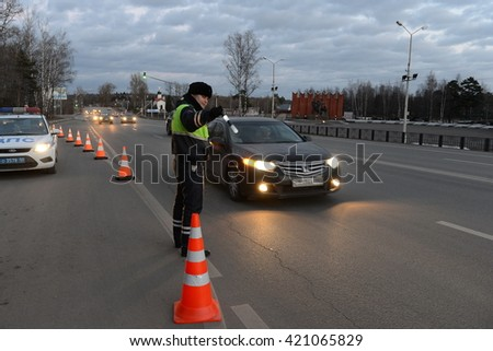 SNEGIRI, RUSSIA - MARCH 14, 2014:The inspector of traffic police stops the car. - stock photo