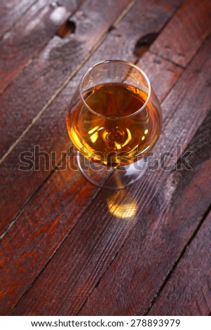 Snifter glass full of brandy standing on a wooden table - stock photo