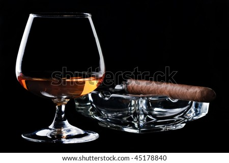 Snifter glass of cognac and cigar - stock photo