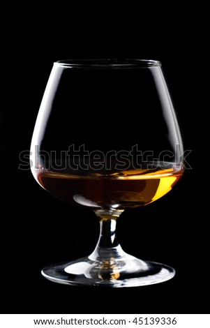 Snifter glass of cognac on black background. - stock photo
