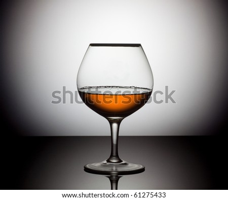 Snifter glass of cognac over circle white and black background - stock photo