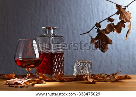 snifter of brandy and dried oak leaves - stock photo