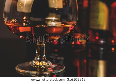 snifter of brandy in elegant typical cognac glass  in front of bottles in background, warm atmosphere - stock photo