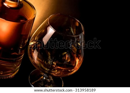 snifter of brandy in elegant typical cognac glass near bottle on black table with space for text - stock photo