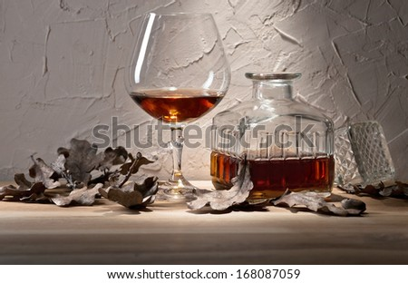 snifter with brandy and dried oak leaves - stock photo