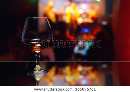 snifter with brandy on glass table in nightclub - stock photo