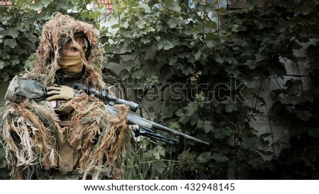 Sniper ghillie suit on the ground, ready to action. Photo edited into warfare look and dark atmosphere.  - stock photo