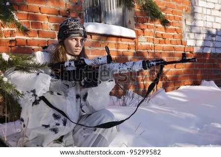 Sniper girl in white camouflage aiming with rifle at winter forest. - stock photo