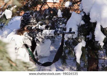 Sniper girl in white camouflage aiming with rifle at winter forest.