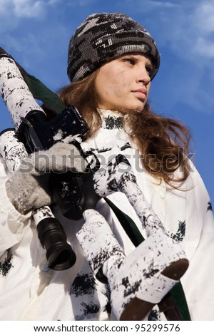 Sniper girl in white camouflage aiming with rifle on a blue sky background - stock photo