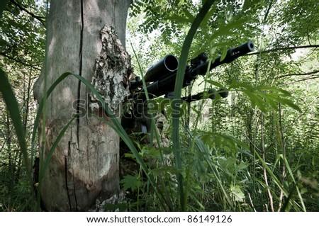 sniper hidden in forest - stock photo