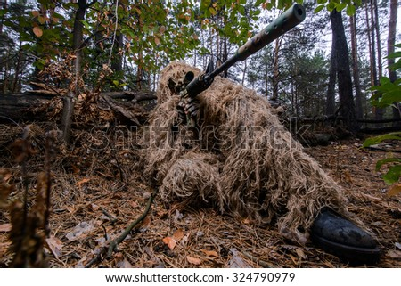 Sniper in camouflage in forest with a rifle aiming at enemy/Camouflaged sniper in forest aiming through scope - stock photo