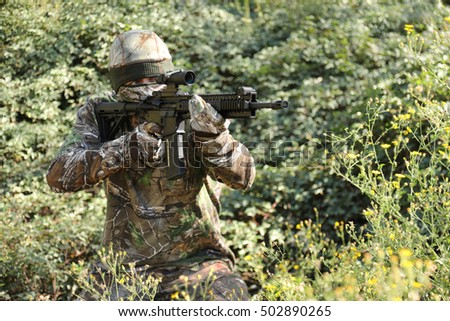 Sniper in heavy overgrowth looking through scope at target