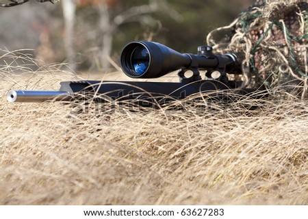 sniper laying on the ground covered in a ghille suite tall grass and trees in the background - stock photo