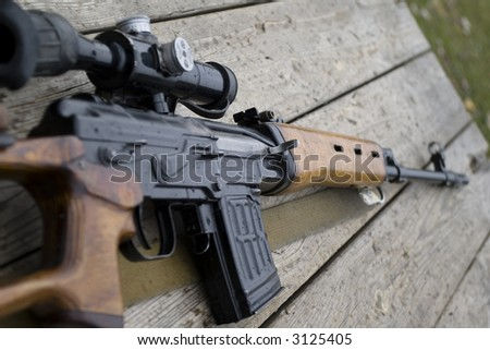 Sniper rifle gun with optical sight  laying on wooden desk close-up - stock photo