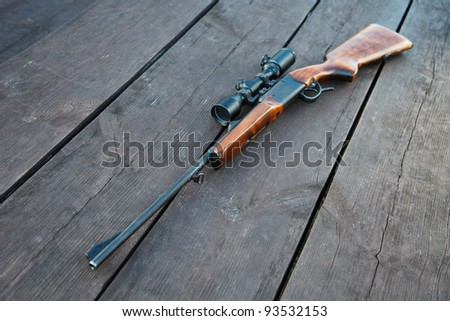 Sniper rifle with optical sight on wooden table. - stock photo