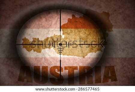 sniper scope aimed at the vintage austrian flag and map - stock photo