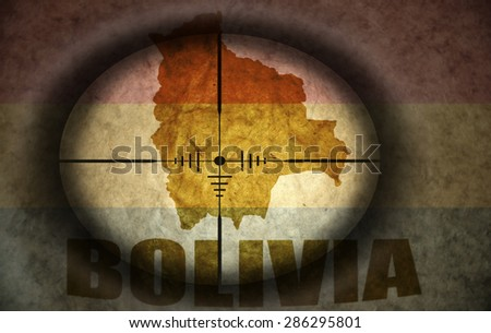 sniper scope aimed at the vintage bolivian flag and map - stock photo