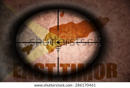 sniper scope aimed at the vintage east timor flag and map - stock photo