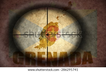 sniper scope aimed at the vintage grenada flag and map - stock photo
