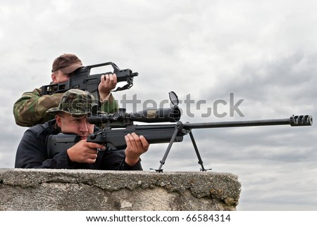 sniper team on the roof - stock photo