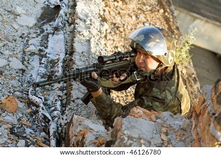 Sniper with a machine gun in an ambush - stock photo