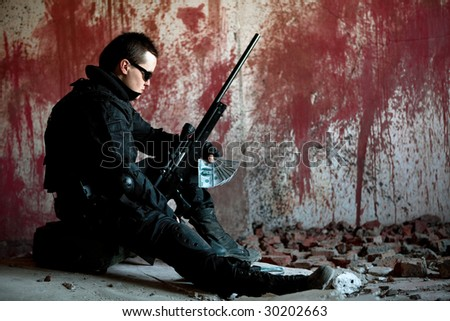 Sniper with rifle and money on the bloody wall background - stock photo