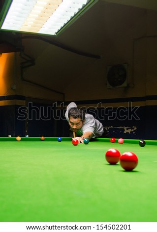 Snooker player placing the cue ball for a shot (Focus on ball,blur on player face and motion blur) - stock photo