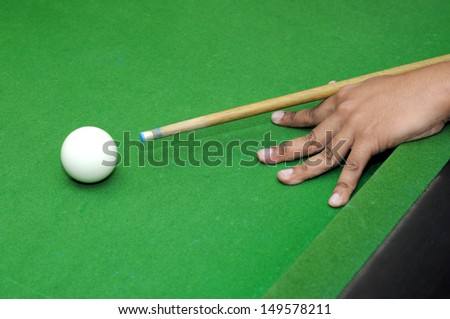 Snooker player with billiard cue ready to hit white ball with selective focus  - stock photo