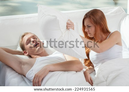 Snoring boy and his girlfriend holding pillow - stock photo
