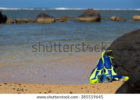 Snorkel and fins by Lava rocks at Anini  beach, on Kauai, Hawaii, ready and  waiting, for the next diving/swimming  adventure.  - stock photo