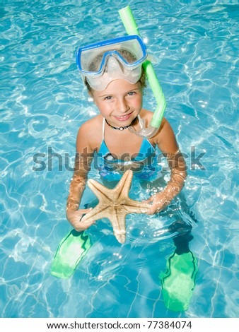 Snorkel girl with starfish in blue water - stock photo