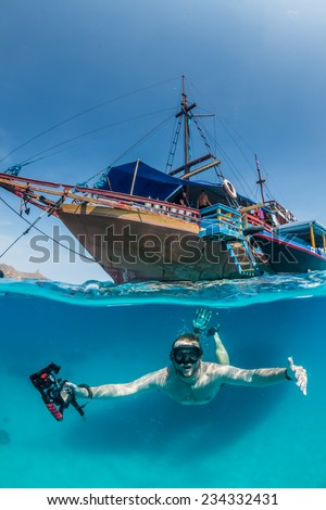 Snorkeler dives under a traditional wooden boat in clear, tropical waters - stock photo