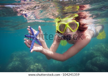 Snorkeler holding blue starfish and looking into camera - stock photo